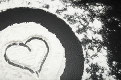 Heart painted on white flour on a black background.  stock photo