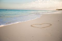 Heart painted in white sand on a tropical beach Stock Photo