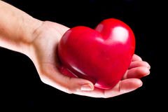 Heart on the palm over black background Stock Photography