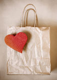 Heart Paper Bag. Worn paper bag with red cardboard heart over wrapping paper royalty free stock image