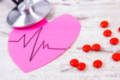 Heart of paper with cardiogram line, stethoscope and supplement pills, medicine and healthcare concept Royalty Free Stock Images