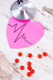 Heart of paper with cardiogram line, stethoscope and supplement pills, medicine and healthcare concept Stock Photo