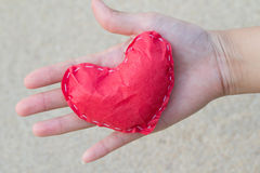 Heart of paper on hand opening up of a young woman. . Showing love stock photo