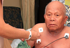 Heart Patient. A sick elderly senior Asian or Filipino man in a hospital room receiving heart diagnosis leads in the upper torso area Royalty Free Stock Photo