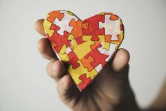 Heart patterned with puzzle pieces, for the autism. Clousep of a young caucasian man holding a heart patterned with many puzzle pieces of different colors Royalty Free Stock Images