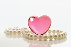 Heart and pearls. Pink heart and pearl necklace over white background Stock Images
