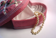 Heart and Pearls. A pink heart shaped box with a string of pearls Royalty Free Stock Photos