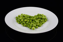 Heart of peas on a white plate. Heart of green peas on a white plate Stock Images