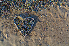 Heart of pebbles on the golden and soft sand Royalty Free Stock Image