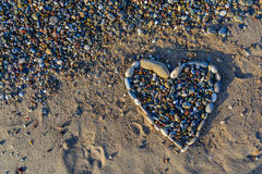 Heart of pebbles on the golden and soft sand on the beach Stock Image