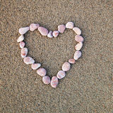 Heart of pebbles inlaid on a background of sand Royalty Free Stock Photography