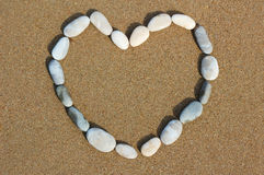 Heart from pebbles on sand Stock Photography