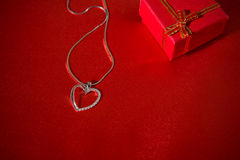 Heart pendant on a red satin background Royalty Free Stock Photo