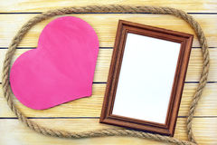 Heart and photo frame on the background of wooden boards Stock Photography