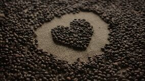 Heart pictogram laid out with dark coffee beans by neat hands with care and love