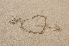 Heart pierced by an arrow drawing on the sand beach. Drawing a heartfelt message for a loved one royalty free stock photography
