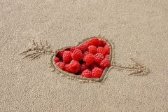 Heart pierced by an arrow drawing on the sand beach inside the r. Aspberries sweet love with sand on the teeth the complex relationship between a man and a woman stock photos