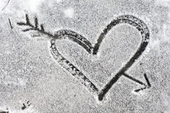 Heart pierced by an arrow drawn with the snow Stock Photography