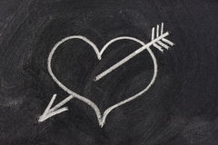 Heart pierced by arrow, love symbol on blackboard. Heart pierced by arrow, a modern symbol of sexual love, sketched with white chalk on blackboard Stock Photos