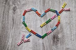 Heart pierced by an arrow made of wooden clothespins Royalty Free Stock Photos