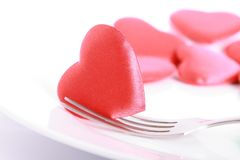 Heart pierced by fork. Red heart pierced by fork on the plate Royalty Free Stock Images