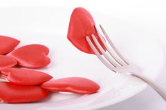 Heart pierced by fork. Red heart pierced by fork on the plate Royalty Free Stock Photos