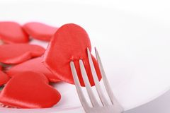 Heart pierced by fork. Red heart pierced by fork on the plate Stock Photo