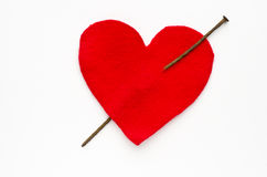 Heart pierced with rusty nail over white background Royalty Free Stock Photos