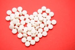 Heart pills. Pills in shape of love heart on red background Stock Photo