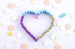 HEART PILLS 2. Pills shaped in the form of a heart on background with assorted pills, capsules and tablets Royalty Free Stock Image