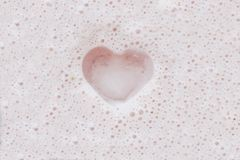 Heart on pink milkshake foam royalty free stock photos