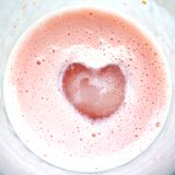 Heart on pink milkshake glass royalty free stock image