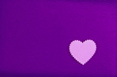 Heart pink on purple leather background Royalty Free Stock Photography