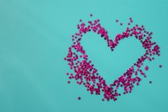Heart of pink stars on a blue background. Inside is empty for text. Flat lay, top view, copy space. stock photography