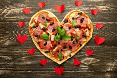 Heart pizza love concept Valentines day romantic dinner Italian pastry with red hearts. on a wooden table. Flat-lay.  stock photography