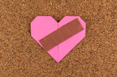 Heart with plaster on corkboard background Stock Photo