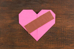 Heart with plaster on wooden background Royalty Free Stock Images