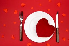 Heart on a plate for dinner. A romantic evening with hearts on red background.  stock photos