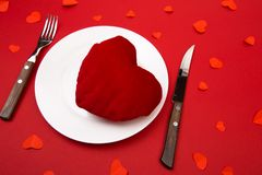 Heart on a plate for dinner. A romantic evening with hearts on red background.  stock images