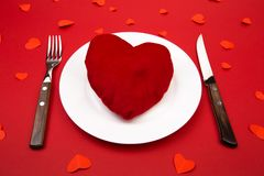 Heart on a plate for dinner. A romantic evening with hearts on red background.  stock photography