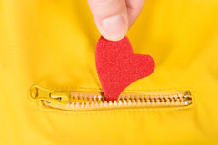Heart in a pocket. Hand putting a red heart inside a pocket Royalty Free Stock Photo