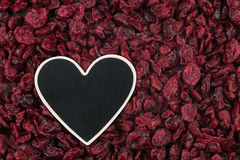 Heart pointer, the price tag lies on dried cranberry Royalty Free Stock Photos