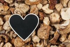 Heart pointer, the price tag lies on dried mushroom Stock Photos