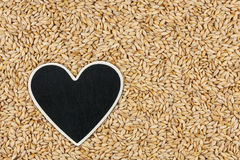 Heart pointer, the price tag lies on grains barley Stock Photos