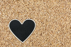Heart pointer, the price tag lies on grains oats Royalty Free Stock Photos