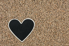 Heart pointer, the price tag lies on grains rye Stock Photo