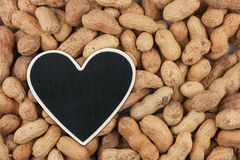 Heart pointer, the price tag lies on peanut Stock Photo