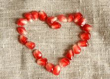 Heart from pomegranate seeds. On a cloth background Royalty Free Stock Photo
