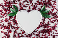 The heart and pomegranate seeds. On the white background. Top view Stock Photos
