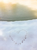 Heart print in the snow. Heart in the snow near the frozen lake Royalty Free Stock Images